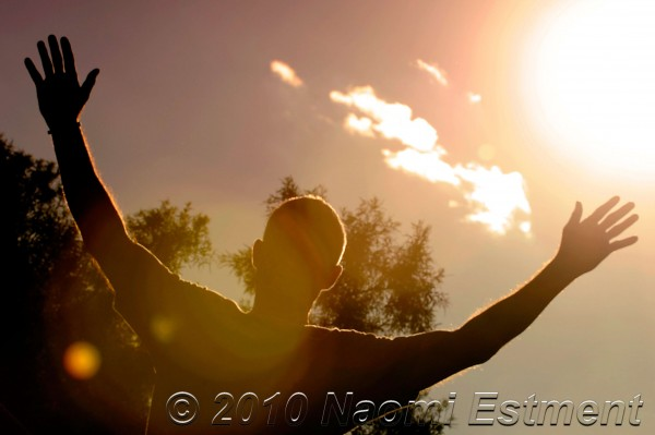 man with arms outstretched towards the sun
