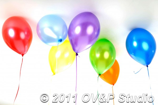 studio photography of model surrounded by balloons