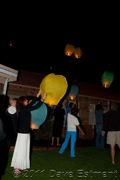 sky lanterns leaving outstretched hands